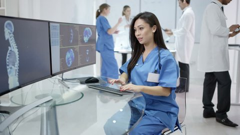 4K Medical team in modern clinic looking at patient scans on computer screens Dec 2016-UK