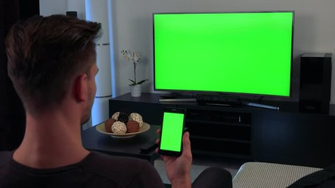 A man turned with the back of his head to the camera watches a TV and eventually glances at a smartphone in his hand, both the TV and the phone have a green screen
