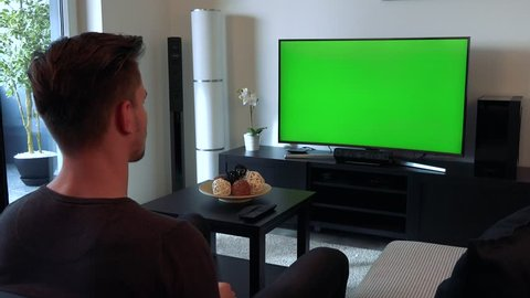 A man watches a TV with a green screen in a cozy living room and then buries his face in his arms, upset and disappointed
