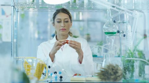 4K Food science researchers working in lab, woman injecting chemicals into fruit Dec 2016-UK