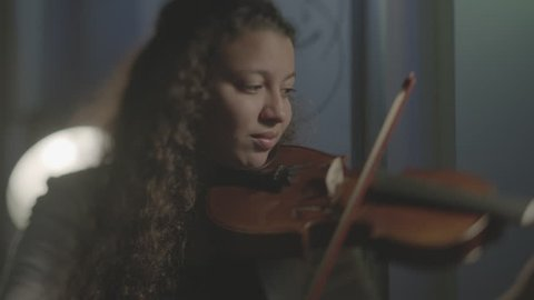 Bahrain - circa 2012 - MCU tracking shot of a young Arab girl playing the violin. Shot raw Arri Alexa.