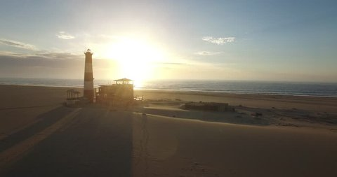 Aerial view from drone video of desert sand peninsula and old lighthouse on seals ocean beach, Walvis Bay lagoon view with sea background and ships at Namibia's Atlantic west coast