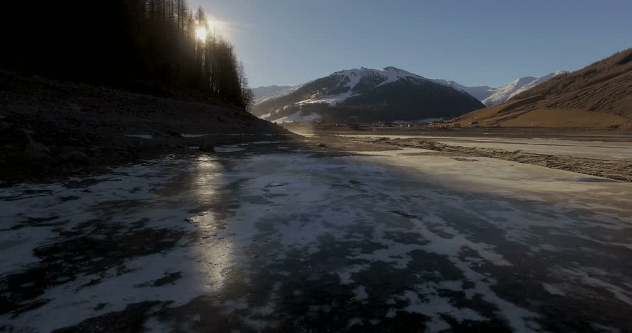river with melting snow, flanked by a frozen lake and the sun of spring that melts #22881505