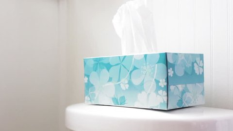 Hand picks out tissue from tissue box in modern bathroom