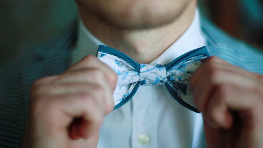 Wearing bow tie close up. Male hands check correct and adjust casual blue bow tie handmade from printed fabrics shallow depth of field. Elegant accessories male fashion macho dandy gentleman concept | Shutterstock HD Video #22917715