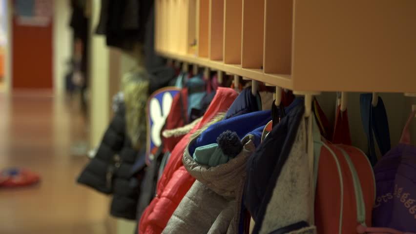 Children's coats and bags hanging from coat rack at primary school, rack focus. | Shutterstock HD Video #22919848