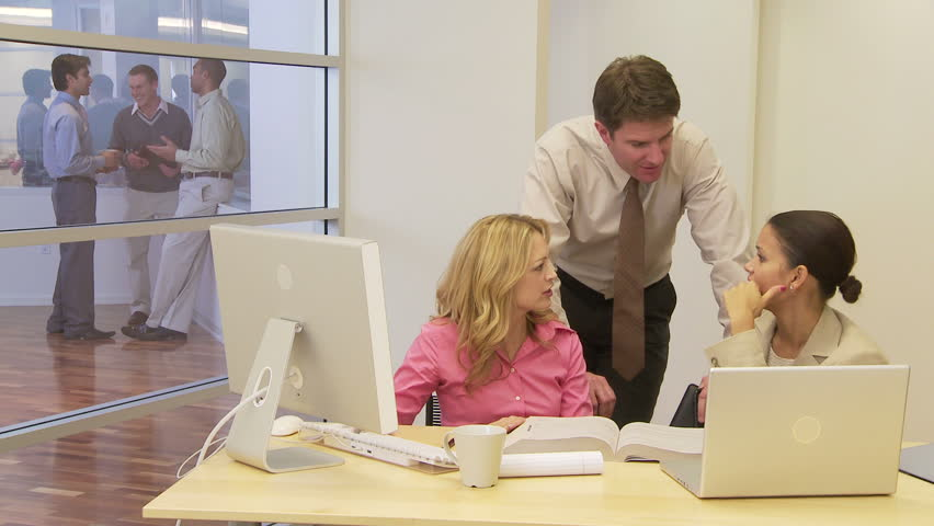 Businesspeople at desk with coworkers in background | Shutterstock HD Video #2292461