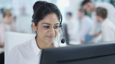 4K Friendly customer service adviser talking to a customer in busy call center Dec 2016-UK