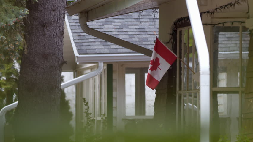 Flag flying outside of suburban house window with foreground.