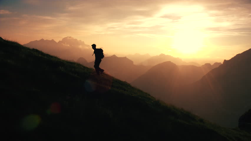 Aerial - Epic shot of a man hiking on the edge of the mountain as a silhouette in beautiful sunset (edited version) #22952905
