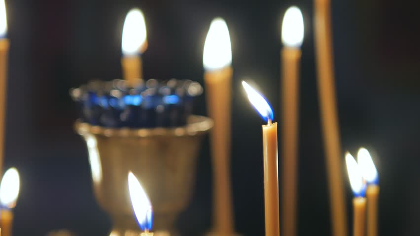 hand lighting. burning candles in an orthodox church icons and prayer 4k stock footage clip hand lighting