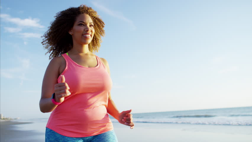 Happy afro hair African American female speed walking along the beach at sunrise for healthcare fitness training RED DRAGON