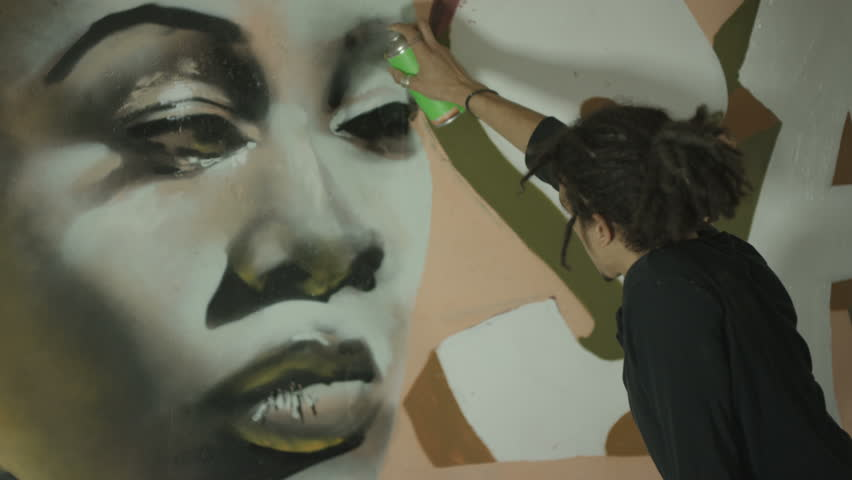 4K Young street artist using different paint mediums to create a mural on wall Dec 2016-UK