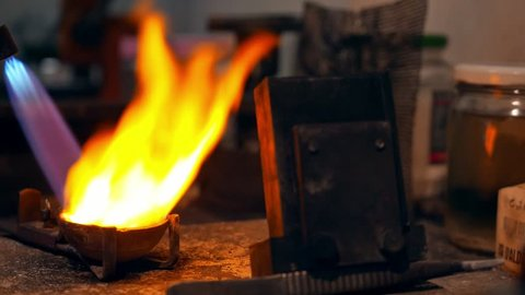 Goldsmith melting gold to liquid state in crucible with gasoline burner