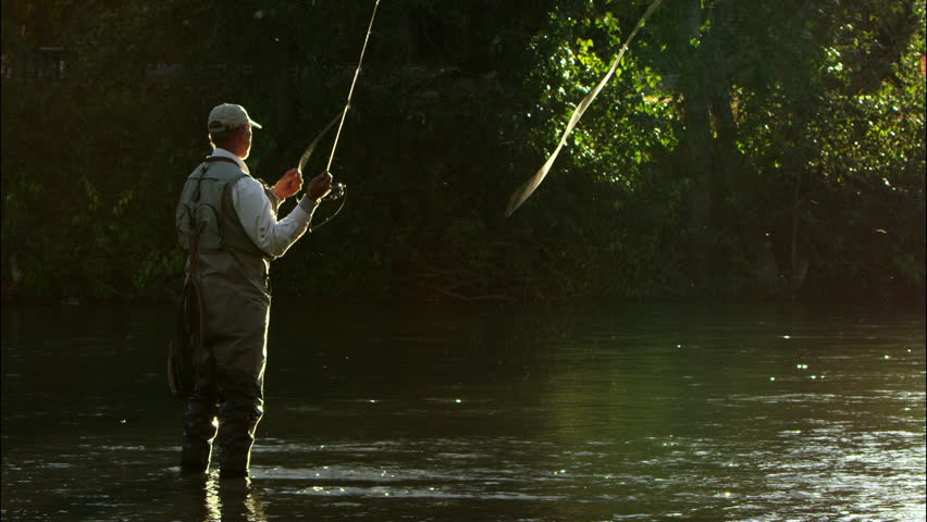 Man fly fishes and sends cast out in evening light. Slow motion (Boise River, Idaho)