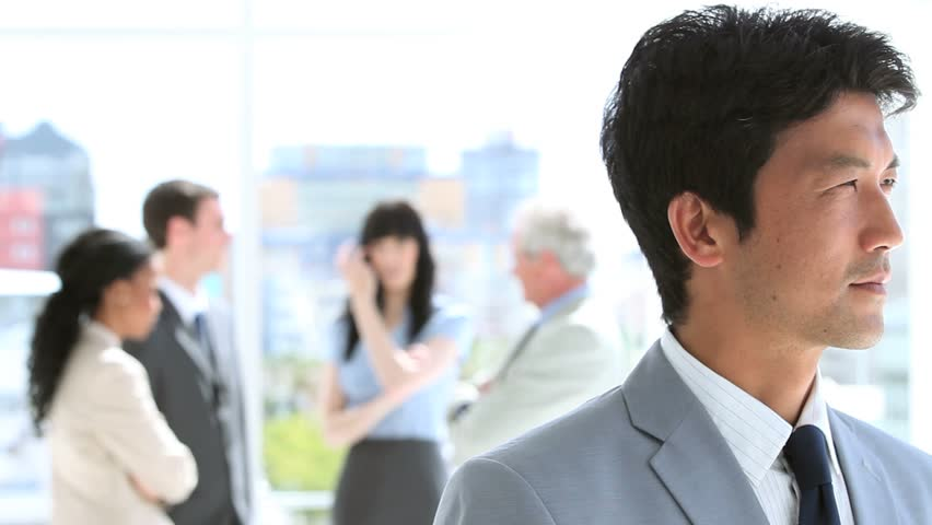 Happy businessman standing upright in front of his team in a bright room | Shutterstock HD Video #2301734
