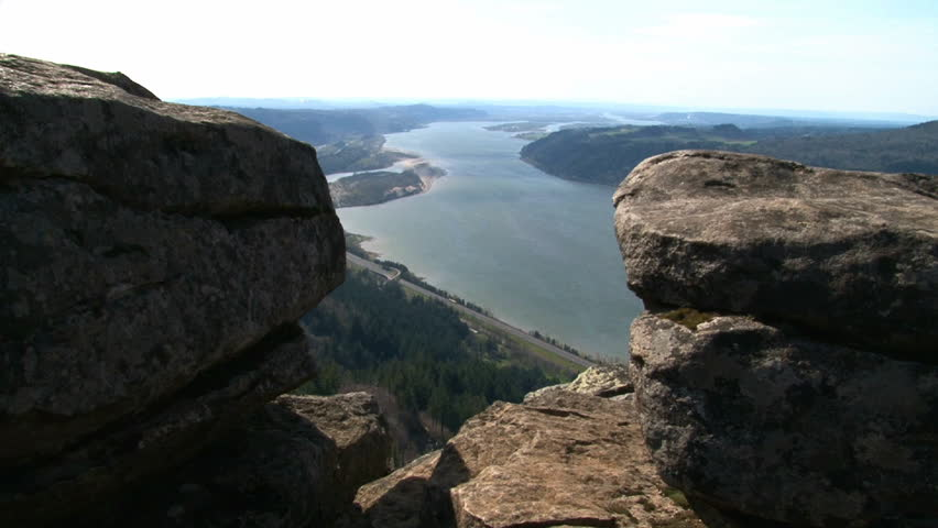 Person hiking and leaping across rocks atop cliff in Oregon up the Gorge. | Shutterstock HD Video #2302526
