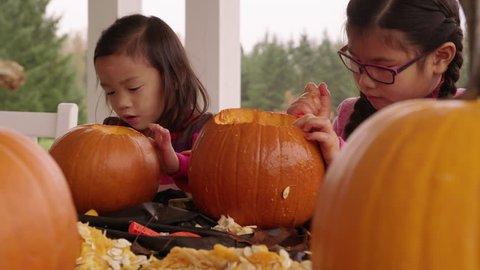Kids carving pumpkins for Halloween