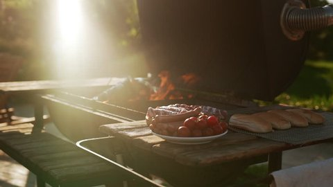 Barbecue grill with burning flame standing near tabel wtih plate of sasuages meat tomatoes and buns outdoors. In slowmotion