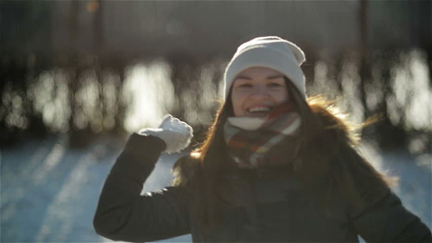 Smiling Girl Enjoying Cold Sunny Morning in the Park. Cheery Active Woman is Throwing Snowball at the Camera Having Fun Outdoors during Winter Time.
