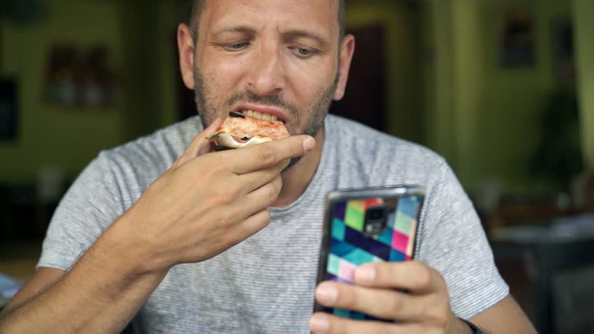 Handsome man sitting with smartphone and pizza in cafe, 4K