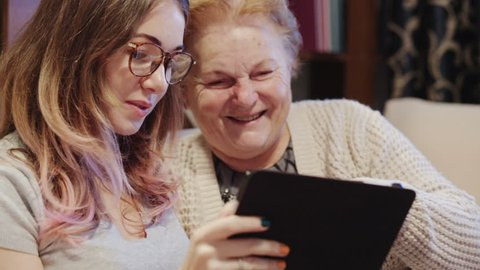 Cheerful young girl with an elderly woman playing together with digital tablet at home