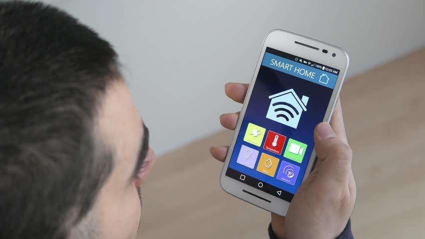 Smart House Phone smart home - man using smarthome app on a smart phone. smart home