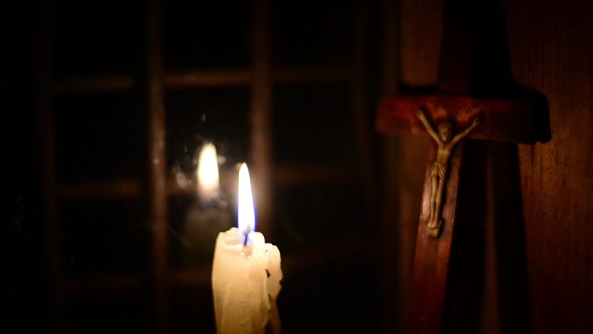 A candle burns on the window. Outside night. The cross with a crucifix standing behind. Candle flame flickers. Wooden windows frame in a wooden house in the mountains.