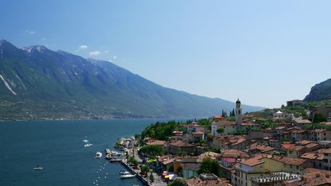 Aerial view of the Limone Sul Garda and Lago di Garda lake. Timelapse with zooming in motion, Northern Italian.