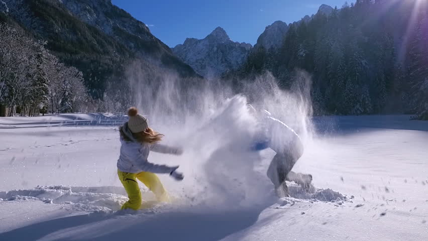 Slow motion - Man grabbing and tossing woman into the snow during a snowball fight | Shutterstock HD Video #23121742