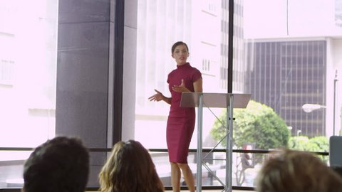 Young woman on stage presenting a business seminar, shot on R3D