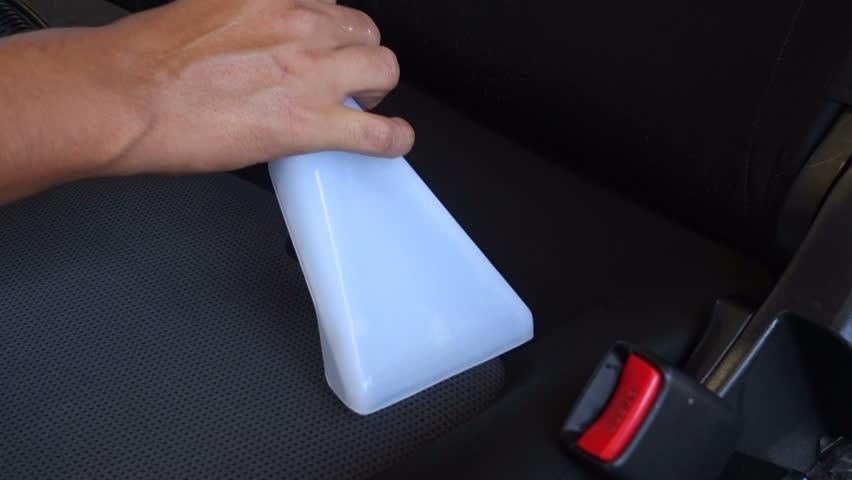 Staff Car vacuuming car seat with vacuum cleaner