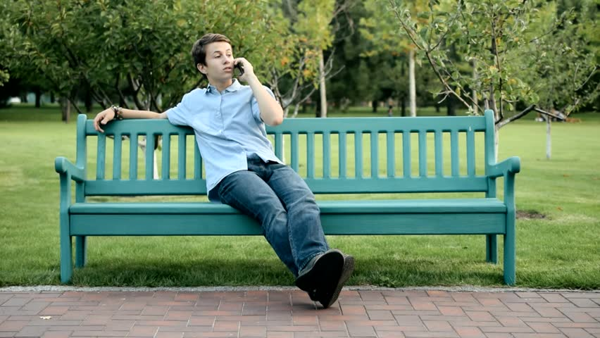 Wonderful Video Bench Part - 8: Teenager Sitting On The Bench In A Park Talking The Mobile Phone In The  Sunny Day