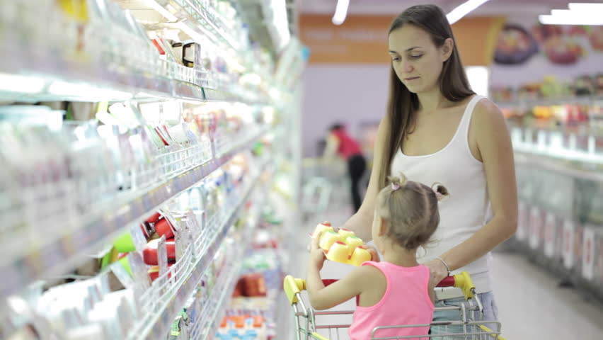 Young attractive woman with cute daughter in shopping cart choosing a yogurt in grocery section at supermarket | Shutterstock HD Video #23156359