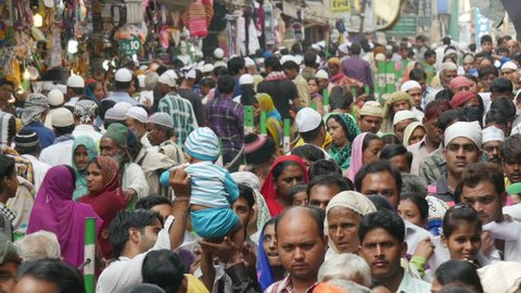AJMER, INDIA - OCTOBER 2014: Massive colorfully dressed crowds walk through a narrow street during the Islamic celebrations of Muharram in Ajmer, India