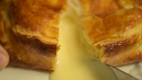 Delicious baked camembert cheese in golden puff pastry cut open and hot melted cheese oozes out of the centre