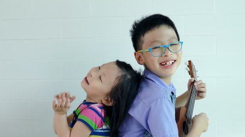 Asian boy play ukulele with his younger sister at home