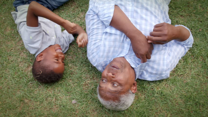 Black grandad and grandson play lying on grass, aerial view