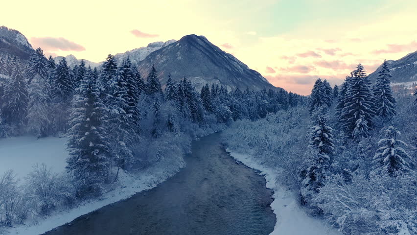Aerial, edited - Fast flight backwards above misty river running through snowy pine forest with mountain in the background