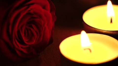 Close up shot of a red rose among tealight candles in the dark. Love concept and Valentine's day theme.