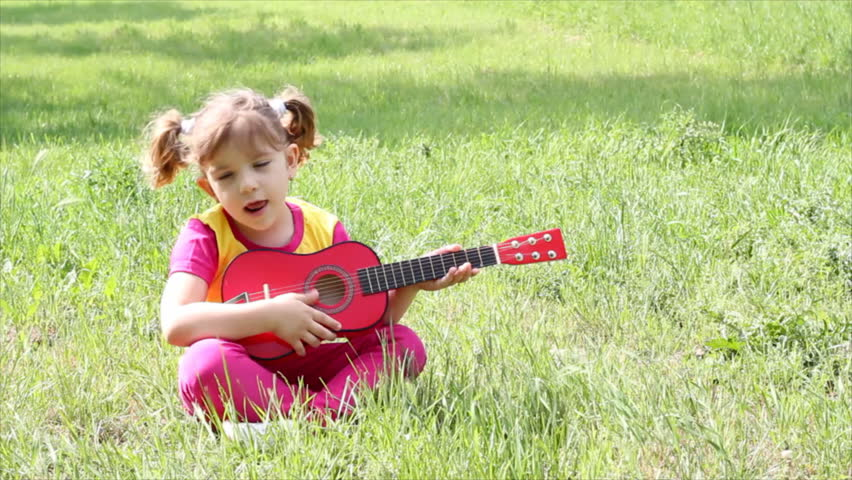 little girl sitting on grass and playing guitar