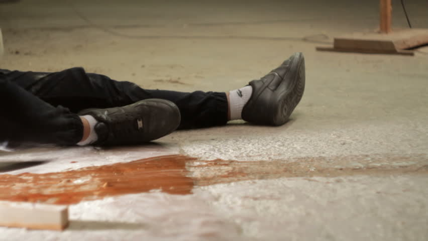 Man with a gun coming to a wounded man. Close-up of legs