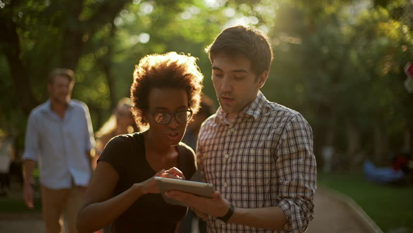 African American female standing in park with Caucasian male with tablet talking while their friends coming giving high fives smiling in slowmotion | Shutterstock HD Video #23236375