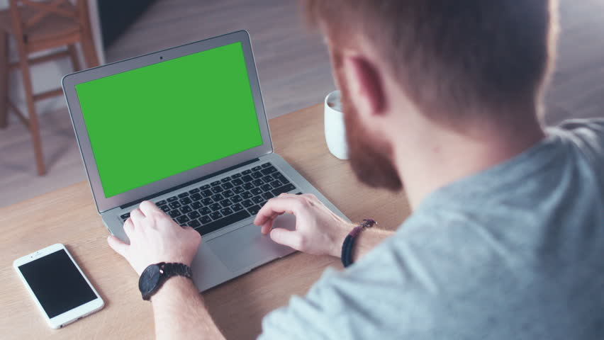 Over the shoulder shot of a young Caucasian man working from home on a laptop, green screen chroma key. 4K UHD 60 FPS slow motion #23252695