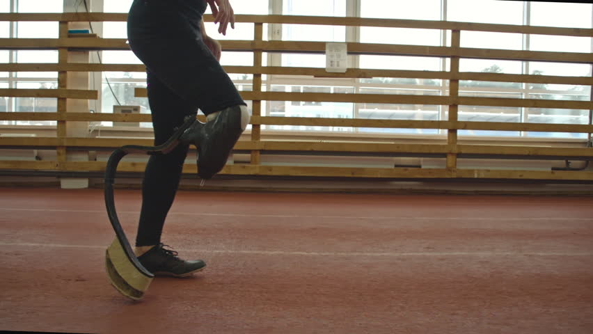 Low section tracking of amputee sportsman with prosthetic leg training on running track in slow motion at indoor stadium