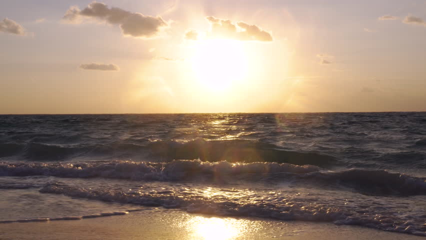 Waves gently wash up onto the beach, then recede as the sun starts to rise | Shutterstock HD Video #23263285