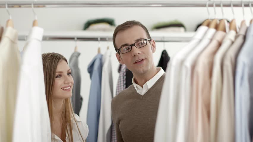 Male customer speaking to sales manager in fashion store while male customer speaking to sales manager in fashion store while shopping for clothes man buying shirt in shop and talking to young woman girl working as altavistaventures Images
