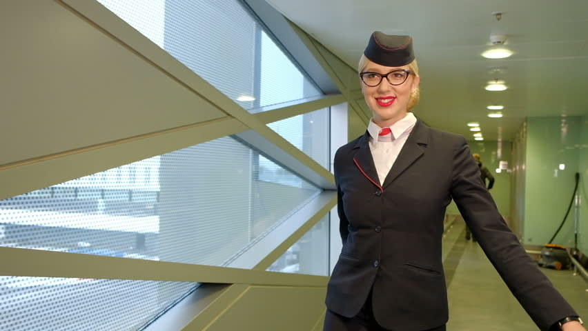 Blonde stewardess walks down hallway at airport terminal indoors. Tall blonde woman dressed in fashionable short blue skirt with red insert, jacket, hat, scarf going down in waiting room. Elegant | Shutterstock HD Video #23287798