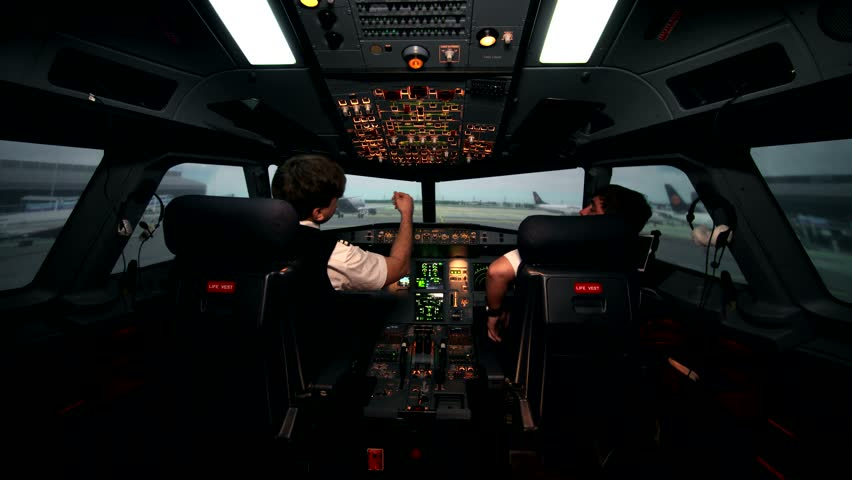 Two caucasian male pilots in the cockpit or flight deck of a passenger airplane switch controls panel of aircraft and prepare for taxiing on the runway before take off on Airbus A319 A320 A321
