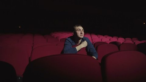 Man sitting in comfortable red chairs in dark cinema theater and applauds